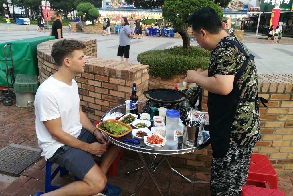A Korean preparing our grill before eating a Korean BBQ